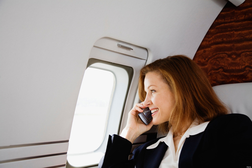 Businesswoman Using Cell Phone on Private Jet