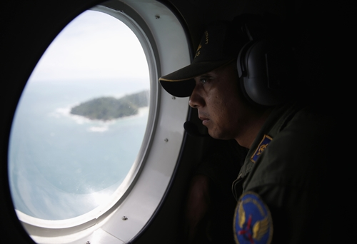 Crew member on an Indonesian Maritime Surveillance looks out the window during a search for AirAsia's Flight QZ8501, north of Bangka island